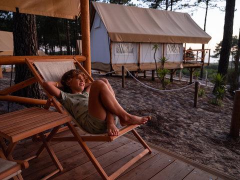 Barefoot boy enjoying on deck chair on beach