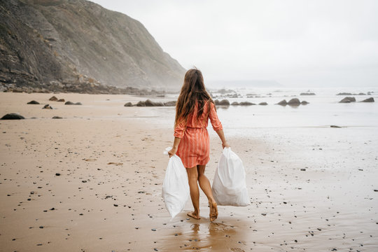Young girl picking up plastic waste from beach