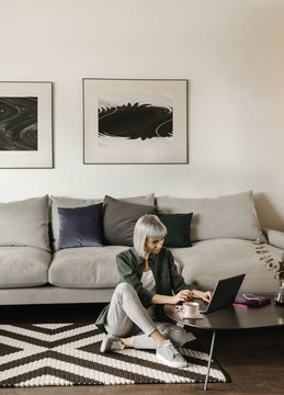 Stylish freelancer using laptop at home