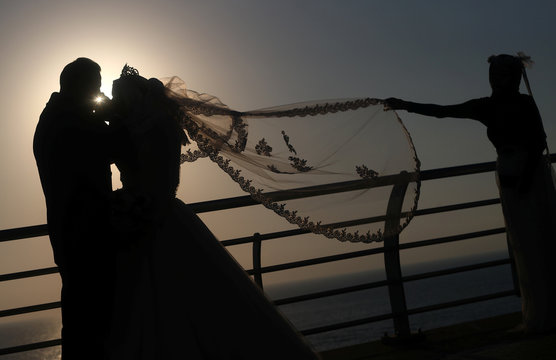 A couple poses for their wedding photos, near the Raouche Rocks in Beirut