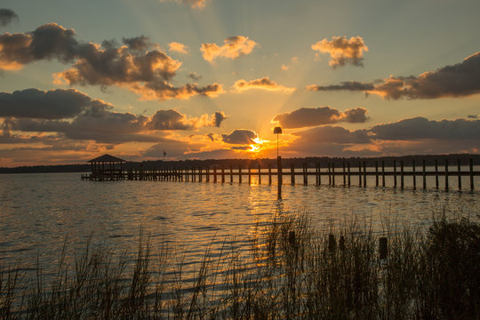 A pier stretching out in Mobile Bay at sunset, at Fairhope Alabama.