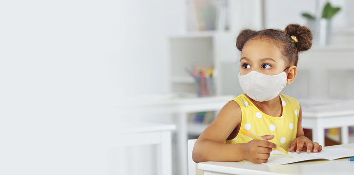 A dark-skinned girl in a medical mask and yellow dress in the school after covid