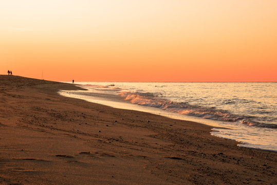 Orange sunset over a sandy beach in autumn. Cape Cod, MA, USA.