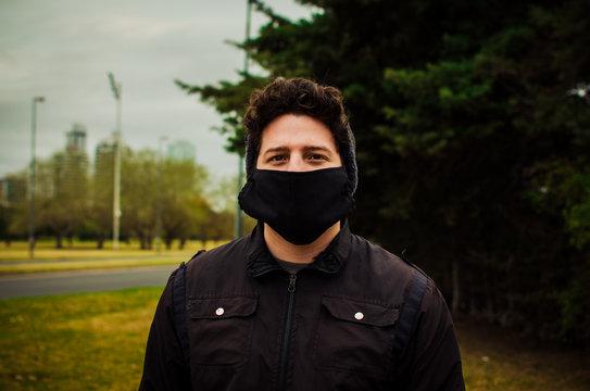 Hombre joven vestido de negro usando mascarilla facial contra el coronavirus. Pandemia. COVID-19.