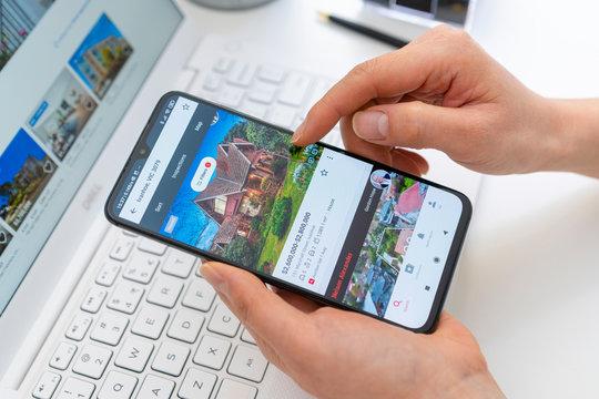 Melbourne, Australia - Jul 28, 2020: Browsing properties for sale in Australia using smartphone app