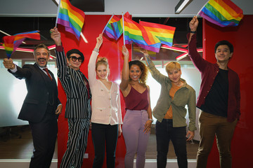 diverse group of lgbtq people with rainbow flag on hand team up together