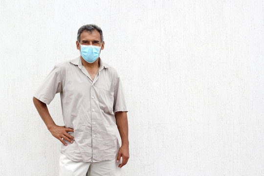 Latino elderly with protective face masks on white wall background, new normal covid-19