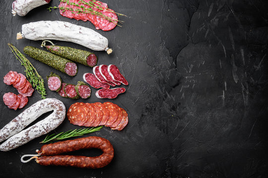Set of dry cured salami, spanish sausages, slices and cuts on black textured surface, topview with space for text