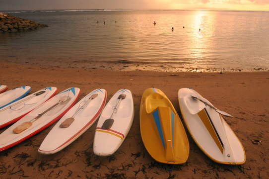 Surfboards line up at sunrise on a paradise beach in Denpasar, Bali, Indonesia