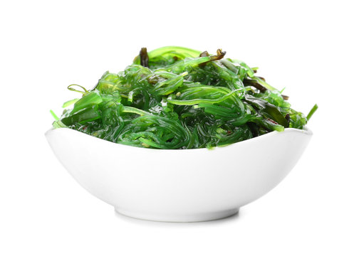 Bowl with tasty seaweed salad on white background