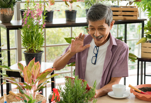 Senior asian retirement old man in casual outfit doing a hobby with happy and relax enjoy drinking coffee and using tablet for video call facetime in greenhouse garden farm
