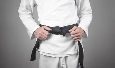 Photo sur Aluminium Combat Caucasian man fixing his black belt. Karate