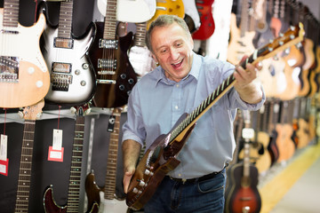 Smiling male demonstrating an electric guitar in a music store