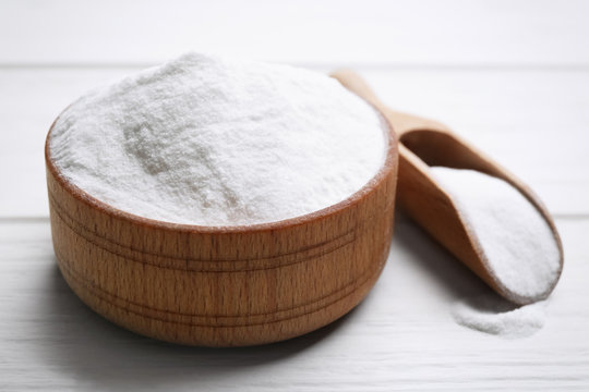 Baking soda in bowl on white wooden table, closeup