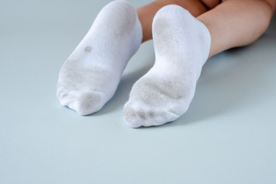 Pair of child feet in dirty stained white socks. dirty socks Pair of child feet in dirty stained white socks. Kid soiled socks while playing outdoors. Children clothes bleaching and.
