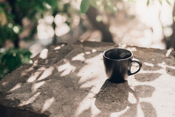 Photo sur Plexiglas Cafe Big black coffee cup at windowsill with leaves shadows in sunny morning.