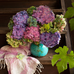 A multi-colored bouquet of hydrangeas in a vase on an old wooden staircase.