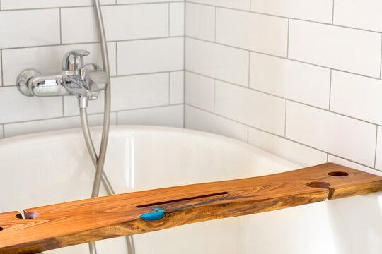 Wooden shelf in white bathtub at home