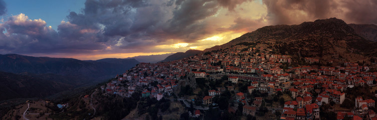 Aerial drone photo of beautiful sunset with golden colours and clouds over picturesque and traditional village of Arachova, Viotia prefecture, Greece