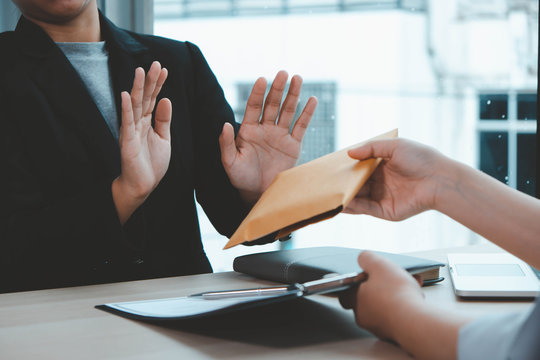 The concept of anti-bribery and corruption. Businessmen refuse and do not receive money banknote offers from businessmen to accept the contract terms of the investment agreement.