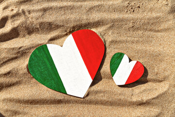 two wooden hearts big and small painted in colors of the flag of Italy green, white and red lies on the golden sand on the beach