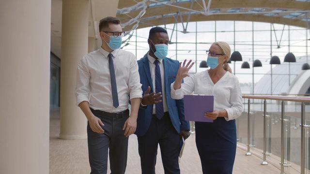 Business team wearing protective masks walking in modern office corridor
