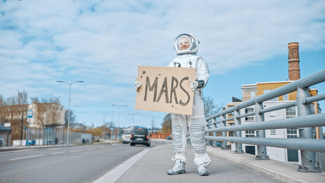 Man in Spacesuit is Standing at the Edge of a Road and Holding a Sign with Mars Written on it. Astronaut Looking to Hitchhike a Car. Spaceman in Futuristic Suit with Technological Panel on His Hand.