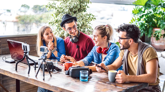 Digital native friends sharing feed on streaming platform with phone and web cam - Content marketing concept with millenial workers having fun vlogging live video on social media space - Bright filter