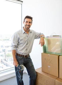 Hispanic man packing cardboard boxes