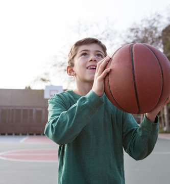 Caucasian boy holding basketball on court