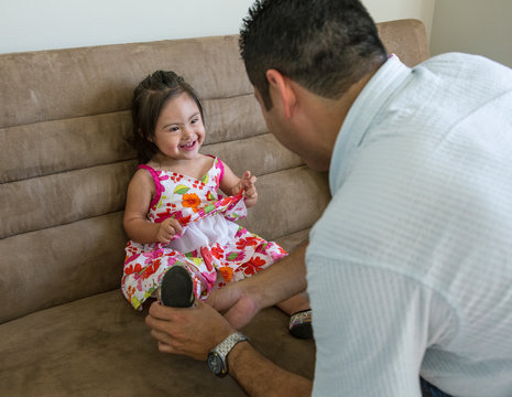Hispanic father helping daughter put on shoes