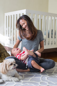 Mixed race mother playing with baby in nursery