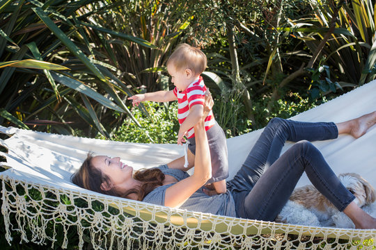 Mixed race mother holding baby in hammock
