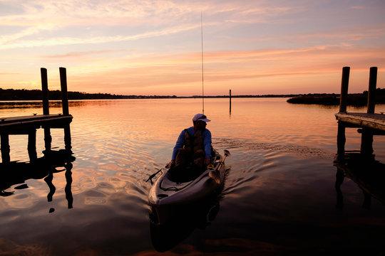 Caucasian man on kayak near dock at sunset