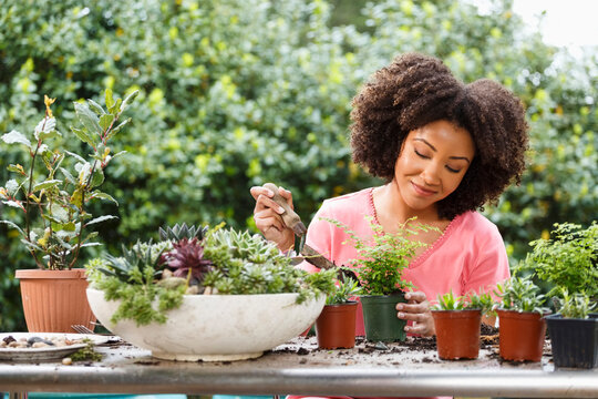 Black woman gardening at table outdoors