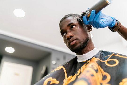 Male hairdresser wearing glove cutting young man's hair with razor in barber shop
