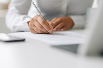 Close-up of businesswoman writing on paper at desk in home office