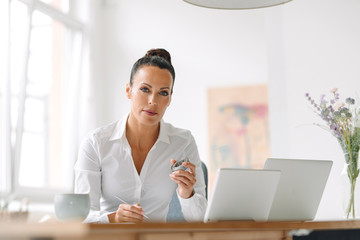 Businesswoman holding metal while working at desk in home office