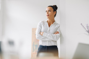 Thoughtful businesswoman with arms crossed standing by wall in home office