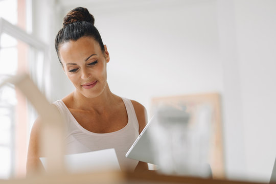 Smiling woman holding digital tablet reading document while sitting at home office