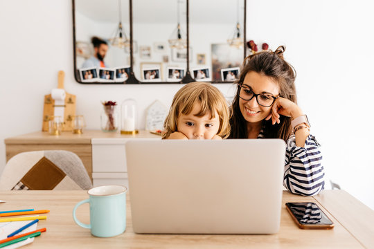 Smiling mother with daughter using laptop on dining table at home