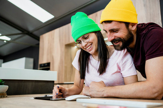 Happy modern business couple using digital tablet at desk in office