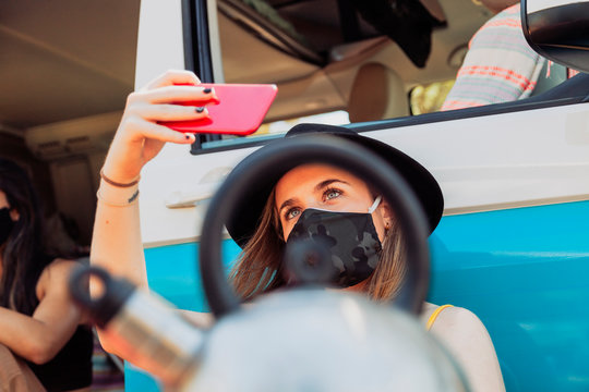 Woman with surgical mask taking selfie during camper van trip