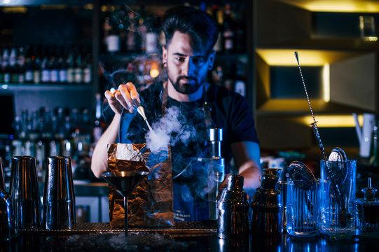 Bartender making cocktail on bar counter in nightclub