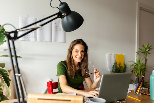 Smiling businesswoman holding eyeglasses sitting at desk in home office