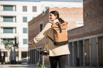Young woman carrying backpack while walking with bicycle on city street