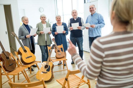 Seniors in retirement home making music singing in choir
