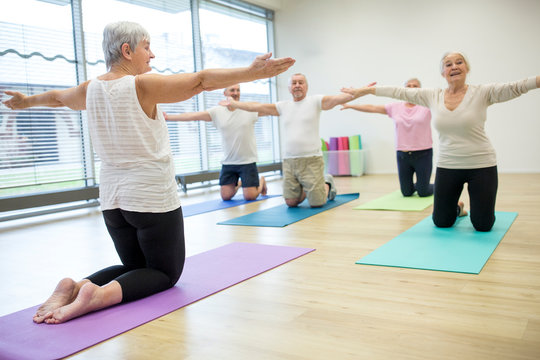 Group of active seniors practicing yoga together