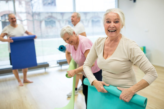 Laughing senior woman rolling up mat after yoga class