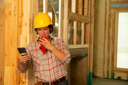 Construction worker on job site feeling ill, sneezing, using mobile phone to check in with tele-medicine doctor